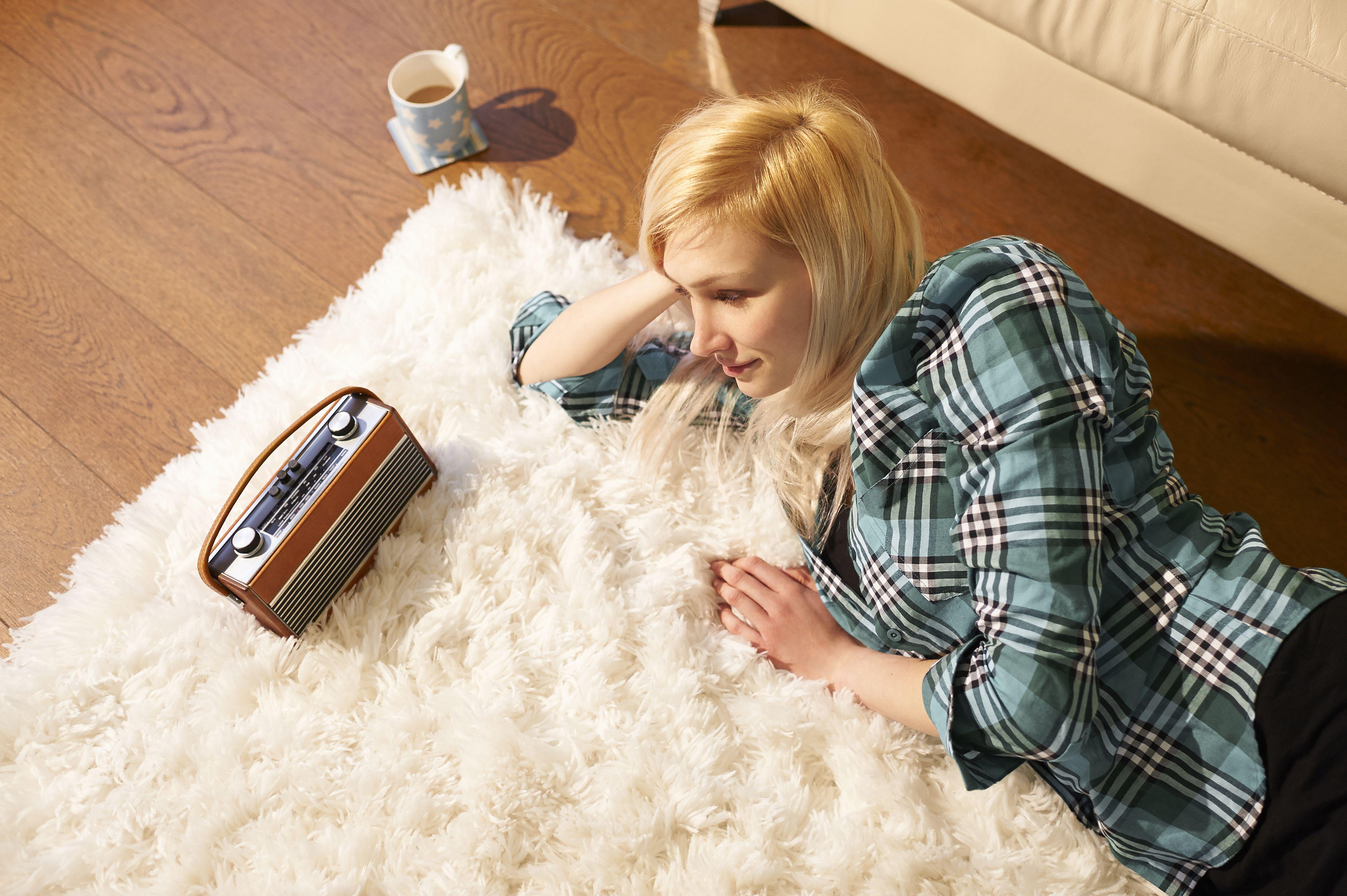 Une femme qui écoute la radio allongée sur un tapis en train d'écouter la radio